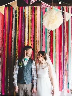 This is a handmade crepe paper fringe streamer backdrop. It is 3 sections of dowels that we put together (easier to transport). We hung from the barn rafters. Perfect for a photo backdrop at your wedding or event! We used it behind our food table, and also cut the cake in front of it. The …