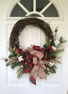 Realistic Douglas fir, cedar and white pine are combined with cotton bolls, heather and clusters of bright red berries to make this warm and welcoming holiday design. The wreath is finished with a double bow of cozy flannel plaid and a gorgeous holiday print ribbon. This wreath is