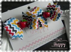 """Few things are sweeter than a little girl with bow-bedecked pigtails! These no-slip Fall Frenzy bows feature adorable apples nestled in the centers of beautiful, full, Autumn-inspired boutique bows. You will love the classic chevron print in vibrant shades of yellow, red, blue, and brown...but you will love the smile on your princess's face while wearing these lovely bows even more! Size: 2.5"""" wide Materials Used: Grosgrain Ribbon Cotton Thread Adhesive Steel Silcone ResinÂ"""