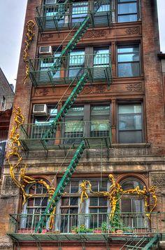 Gold sculptures climbing up, NewYork