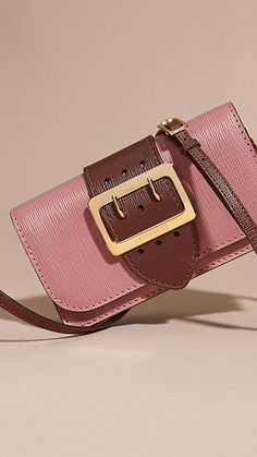 The Buckle Bag in textured leather from Burberry in dusky pink. Made in Italy, the design has a regimental belt detail with a polished gold metal buckle referencing the trench coat.