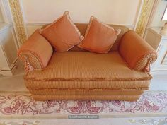Lot 935 - A two seater heavy padded upholstered sofa low back scroll arms in gold draylon type fabric 700mm