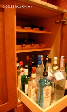 Roll-out and inserts for bottle storage in a liquor cabinet.