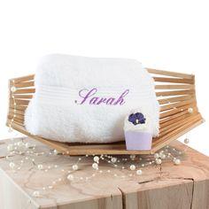 Das persönliche Wellness-Set enthält ein wunderbar weiches Handtuch aus Baumwolle und einen handgemachten Badetrüffel. Es kann durch einen aufgestickten Wunschnamen auf dem Handtuch in der Farbe Lila personalisiert werden.
