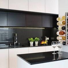 Biało czarna kuchnia, w której nie tylko blat ale cała wnęka została wyłożona czarnym konglomeratem kwarcowym.