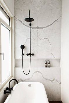 Subway tiles paired with a black grout complement the dark steel elements of this rustic space. A nearly exclusive concrete surround inspires simplicity in this stylish walk-in. Subway tiles, a pop of