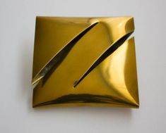 """Cushion"" by Françoise van den Bosch. 1973. With two diagonal slits. yellow brass."