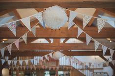 A Vintage Floral Chintz and 1950s Inspired Pretty Pastel Pink Wedding. Paper balls between the bunting