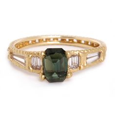 This handcrafted ring features an inverse cast emerald green sapphire gem, bordered by princess-cut and tapered baguette diamonds.  It is a gorgeous and unique choice for an alternative engagement ring.    Diamonds:  1.00 total carat weight Sapphire:  1.25 ct. Metals:  18k yellow gold Currently available in a size 6.75.  Other sizes must be special ordered. Handmade, Imported    Item number:  202-01720