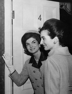 Jackie Kennedy smiles for admirers gathered to catch a glimpse of the First lady as she enters the home of her sister, Princess Lee Radziwill, to select a costume for the big event of her three-day London visit- lunch with Queen Elizabeth at Buckingham Palace on March 28th. March 27, 1962