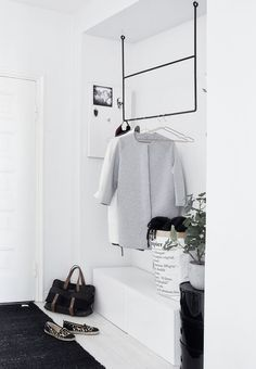 Black clothing rail and sleek drawers in the hallway of the Helsinki home of…
