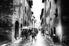 Rainy day San Gimignano - A rainy day in the beautiful old town of San Gimignano / Tuscany. People with and without umbrellas go through an alley with beautiful historic buildings. Impressionist street photography in black and white. #photography #blackwhite #street #streetphotography #fineart #fineartphotography #tuscany