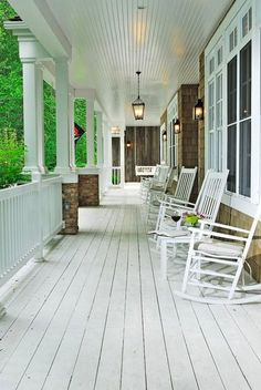 Gorgeous porch with white washed wood plank floors, white rocking chairs and black lanterns.
