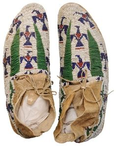 native american, America, Pair [Native American Indian] sinew-sewn beaded hide moccasins, probably Cheyenne, 20th century, stitched with numerous shades of opaque and translucent beads, pairs of triangles and stylized eagles in red and navy blue, wavy beadwork at ankles, rawhide soles.