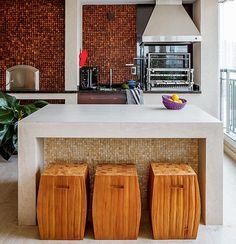 """A cozinha gourmet tem churrasqueira. A parede acima da bancada de granito preto possui pastilhas de coco. """"Troquei a coifa pelo modelo com sistema de exaustão, que é mais eficiente para a churrasqueira de carvão"""", diz a arquiteta Erica Mare."""