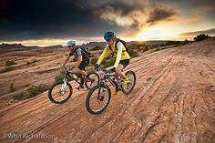 A couple mountain biking on a rock formation near Moab, Utah. by…