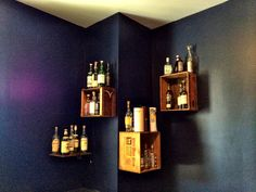 Scotch whisky bottle collection with Scotch whisky crates as shelves. But of course, it works just as well for bourbon, regular whiskey, etc.  On the left side is a single shelf made from the side of a Jack Daniels crate, repurposing the hinges as wall mounting hardware. The top, which formerly had the hinges, was secured in place to keep the 2-level thing going.  Scotch bottles were collected over about 9 years and represent some very dear experiences. Lagavulin, Laphroaig, Port Ellen, and…