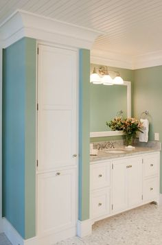 Bathroom with custom white vanity, linen cupboard with pullout hamper, white beadboard plank ceiling, cove molding, and walls painted seafoam green - Crown Point Cabinetry - crown-point.com
