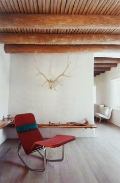 Georgia O'keefe, red lounge chair, white walls, wooden bench, wood installation