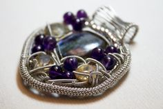 This wire wrap contains a lovely peice of labradorite surounded by syberian amethysts, 1 sunstone, 1 smokey quatz and 1 champagne topaz.