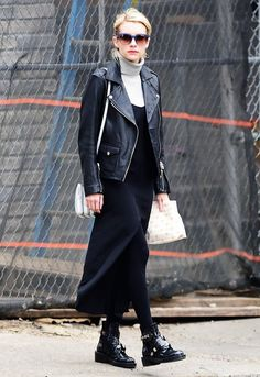 Emma Roberts wears a turtleneck, long slip dress, leather moto jacket, tights, Balenciaga boots, square sunglasses, and a shoulder bag