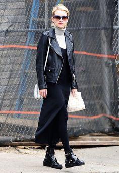 Emma Roberts wears a turtleneck, long slip dress, leather moto jacket, tights, Balenciaga boots, square sunglasses, and a shoulder bag