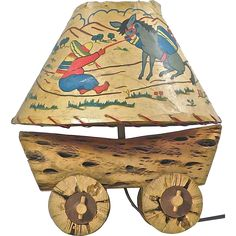 Vintage; 1910-1950, Mid-Century Modern, Southwestern cactus wagon table lamp with paper shade depicting a man pulling a mule. Wired and in working