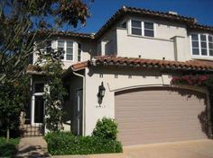 With dark brown trim under roof, porch railings, and shutters