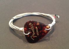 Une main recyclé guitare string bracelet/bracelet avec un plectre de fender.