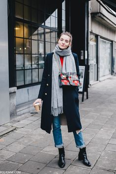 Paulien Riemis is cute and casual in this stylish winter look, consisting of rolled denim jeans, a double breasted navy overcoat, and a pair of striking patent leather boots. Tee: H&M, Cardigan/Boots: Zara, Coat: River Island, Bag: Pinko.