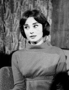"""The actress Audrey Hepburn photographed during an interview at the London Airport (known as """"Heathrow Airport"""" since 1965) in London (England), on November 16, 1956. Audrey was wearing: • Dress (with matching thin belt of suede): Givenchy (of wool in..."""