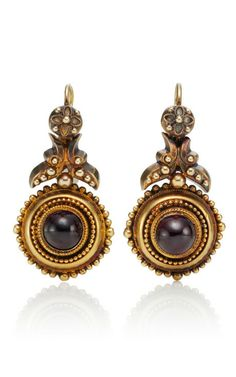 These antique, circular shield inspired drop earrings date back to the 1880's and feature a cabochon garnet center with a beaded border and Etruscan style appliques at the top Wire hook for pierced ears 14k yellow gold