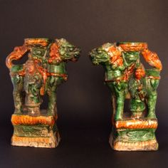A Pair of Ming Pottery Glazed Taper-stick Holders, Late Ming c.1550-1640. Modelled as Buddhist Lions Surmounted by Lotus Decorated Taper-stick Holders with Attendants. The Rectangular Bases with a Recessed Central Section Decorated with Impressed Designs Including `Cash` Emblems. The Lead Glazes are of Green and Ochre.