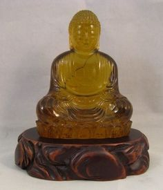 Vintage Amber Glass Buddha Figure on Carved Stand. For sale at Eastern Shore Antiques. 1410 US Hwy 98  Suite A Daphne, Al 36526