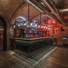 Industrial bar, exposed brick, dark wood, exposed vents, red lighting Trafiq Bar in Budapest