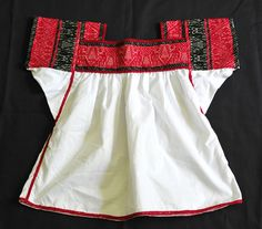 This is a woman's blouse from Santa Ana Tzacuala, a Nahua community in the municipio of Acaxochitlan, Hidalgo Mexico. I was told by a local clothing shop owner that 4 unique styles of blouses are worn by women from Tzacuala.