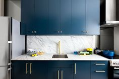 The marble countertops and backsplash, gold hardware, crystal knobs, and rich blue cabinetry make for a classy and timeless kitchen.