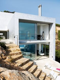 Situated eight miles from Barcelona, this home, Casa Nuria Amat, by Jordi Garces, is four hundred and fifty square feet of beautiful jaw-dropping space. The cliff it sits on is integrated into the design, fashioning a unique Spanish house. The rectangular shape is absolutely gorgeous with its floor to ceiling windows and cool exterior. The warm stone steps look positively amazing next to the cool colored home.