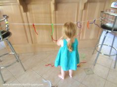 """Challenge your toddler's creativity, problem solving and fine motor skills with this """"Pipe Cleaners on a String"""" activity"""