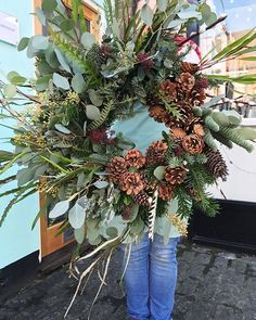 Christmas and autumn wreaths are my absolute favourite thing to make. This asymetrical door wreath is packed with seasonal foliage including pine, eucalyptus, skimmia and decorated with a ton of pinecones. pinecones and dried fruits. Christmas Door Wreaths, Christmas Swags, Christmas Door Decorations, Christmas Flowers, Natural Christmas, Autumn Wreaths, Christmas Centerpieces, Holiday Wreaths, Inspiration