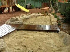 Beautiful sand pit using organic lines. Love the warmth the dark wood adds too.