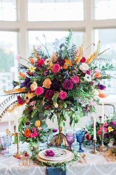 For a colorful boho-chic wedding - centerpieces of garden roses in magenta, fuchsia, blush, and peach, as well as pops of orange tulips and purple anemones and hellebore ~ https://www.insideweddings.com/weddings/vibrant-styled-shoot-with-colorful-bohemian-inspired-details/793/