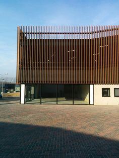 Shopping mall: vertically corten steel blinds, aluminum frames. Winkelcentrum: verticale cortenstalen lamellen gevel, aluminium kozijnen.