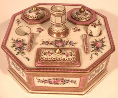 A DRESDEN PORCELAIN LADY'S WRITING DESK SET. of octagonal form, hand painted, with covered twin stamp well, twin removable ink wells with covers, wax seal stamp, both upright and horizontal pen holders.