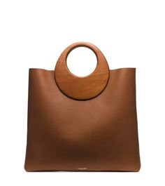 Infuse polished looks with an artful edge. Sculpted wooden handles crown this minimalist tote with a mod twist. Its roomy interior and buttery-soft leather design make this go-to carryall a refined statement piece. Handbags Michael Kors, Tote Handbags, Purses And Handbags, Clutch Bags, Fossil Handbags, Leather Purses, Leather Handbags, Leather Totes, Leather Bags