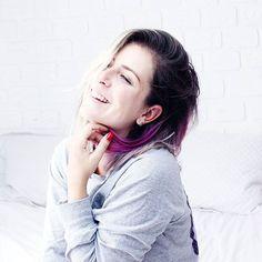 Foto sentada nca mada em um quarto iluminado com decoração clean, em frente a uma parede de tijolinhos, segurando uma mecha de cabelo magenta