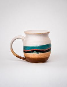Warm beverages have never been so appealing as when sipped from these handmade ceramic mugs. Artfully crafted by a husband and wife team, these mugs are made of stoneware clay, and each piece is hand