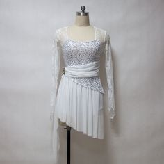 Stunning lyrical costume! Built on a white leotard with silver sequins, this elegant lyrical dress features white lace long sleeves and a square neck. The chiffon white skirt is cut diagonally to mimi