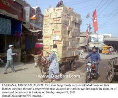 Two men dangerously carry overloaded boxes on their donkey-cart in Larkana.jpg
