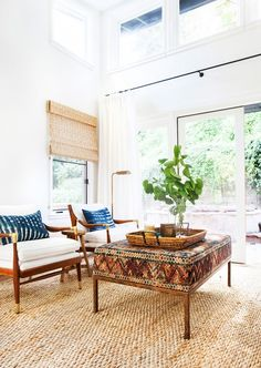 Bedroom seating area with white arm chairs and natural fiber woven rug.